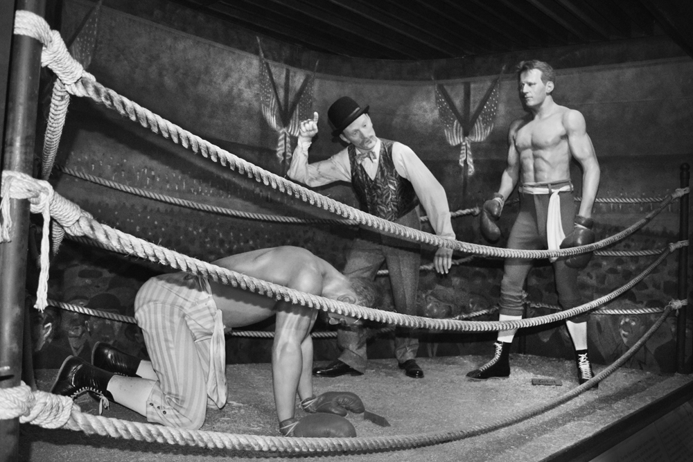 Black and white photo outside boxing ring ropes shows Musee Conti wax figure display of Jim Corbett knocking out John L. Sullivan and referee calling the match on September 7, 1892 at the Olympic Club on Chartres Street in the New Orleans Bywater neighborhood.