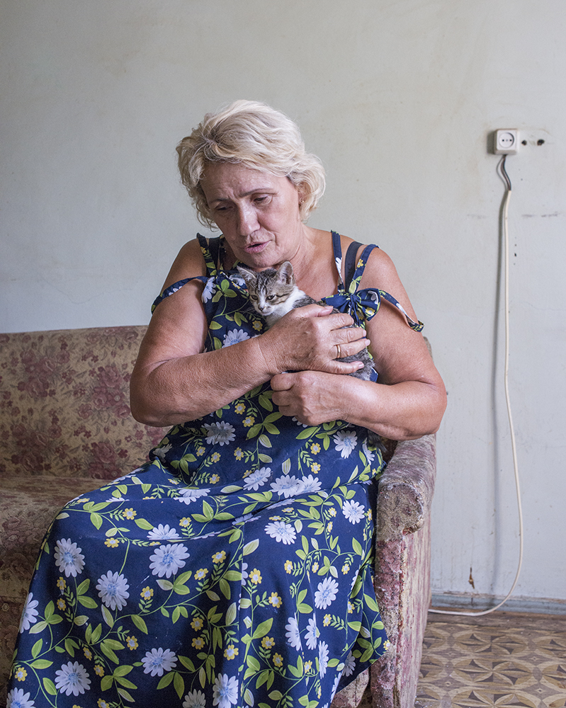 "Marie, 70, lives in the govdernment-assisted shelter Collective Center after fleeing shelling in the east. ""This kitten is named Mariska. She heals me by taking away bad energy."""