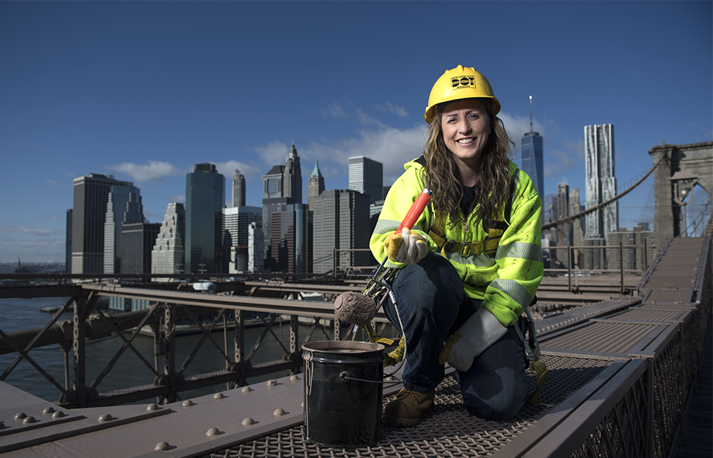 "ELISANGELA OLIVEIRA, a bridge painter for the New York City Department of Transportation. ""I've been doing this for 18 years since I was 19-years-old. I started out in an apprenticeship program with the Bridge Painters Union, Local 806. After three years as an apprentice, I became a journeywoman, and then a forewoman. After that, I worked as a supervisor and in quality control. I did a lot of big jobs for many years. I believe that women can do anything. Whatever men can do, women can do. Women can build, and do things like paint bridges because we have the strength and the patience."""