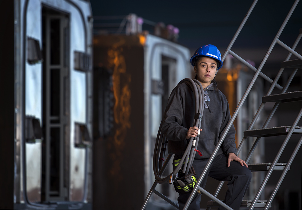 "RUBY DIAZ, a quality control technician at the Kinkisharyo railcar factory in Palmdale, California. Ruby works on running and routing electrical wires through metal pipes throughout the railcars.  ""When I was little, I learned how to fix stuff; I had my own little motor scooter. [This work is] hard for women, they feel they don't have enough strength, or power, or dedication. [While] it is a tough and heavy job, women can work just as hard as anybody."""