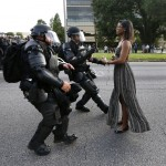 Lone activist Ieshia Evans stands her ground while offering her hands for arrest as she is charged by riot police during a protest against police brutality outside the Baton Rouge Police Department in Louisiana, U.S.A. on July 9, 2016. Evans, a 27-year-old Pennsylvania nurse and mother to a young boy, traveled to Baton Rouge to protest the shooting of Alton Sterling, a 37-year-black man and father of five, who was held down by two white police officers and shot at close range by one of the officers. The shooting, captured on cell phone videos, aggravated the unrest that has coursed through the United States for two years over the use of excessive force by police, especially against black men. REUTERS/Jonathan Bachman