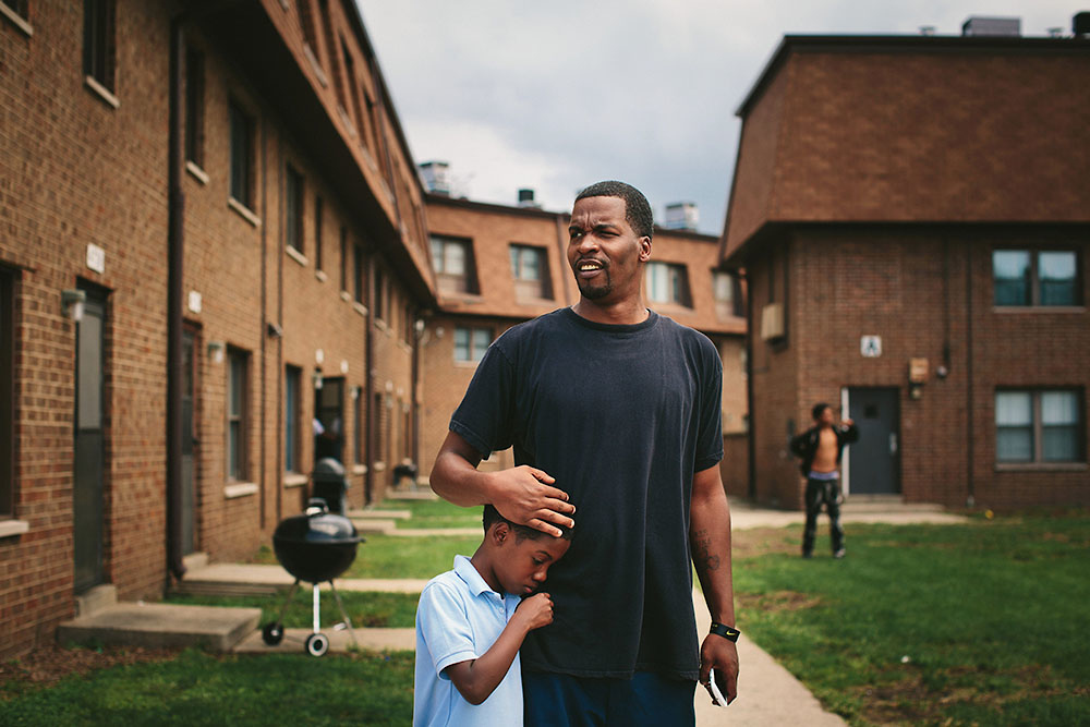 Lamont Anderson embraces his son Lamont Anderson Jr., 8, at the West Calumet Housing Complex. Anderson Jr.'s blood lead levels test results were above the CDCís 5 mg/d threshold for action. After living in the complex for more than a decade, the family moved to Gary, Indiana earlier this summer.  |||| American industry disproportionately affects the health of minority and low-income communities, and East Chicago, Ind. ó known as the countryís ìmost industrialized municipalityî during the Industrial Revolution ó offers a view of environmental injustices emerging throughout the Rust Belt.