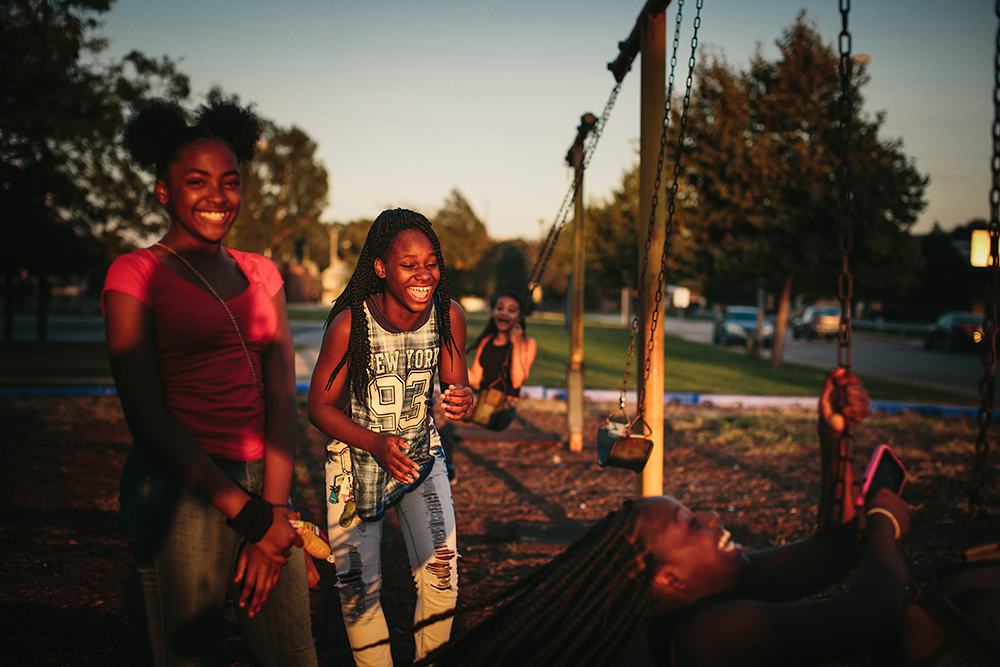 "From left, friends since childhood, Janae Peyton, 13, Ashanti France, 12, Irene Wooley, 13, and Tniyah Foxx, 12, swing at the park near the West Calumet Housing Complex in East Chicago, Indiana. The playground is part of the Carrie Gosch Elementary School, which has been turned into an EPA office. ""All my memories are here. I've got to move away from my friends,"" Peyton said.  