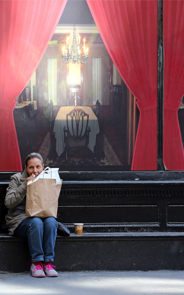New York Street Scene--Woman eating lunch on 19th street in front of a mural of a dining room table. Exclusive photo by Lawrence Schwartzwald