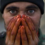 An Afghan soldier seen warming his henna stained hands from EID worship on the front lines in Zhari District, Kandahar, Afghanistan.  (Credit Image: © Louie Palu/ZUMA Press) FROM THE BOOK FRONT TOWARDS ENEMY. USE RESTRICTED TO BOOK REVIEWS ONLY