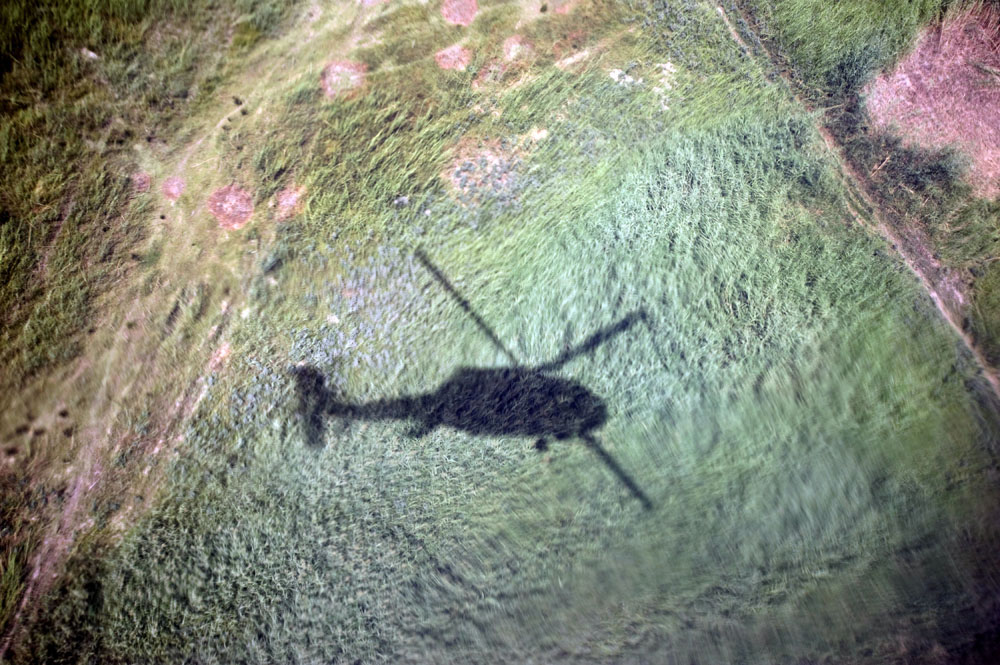 The shadow of a US Army Medevac helicopter is seen in a field as it prepares to land in a field to evacuate a casualty who was hit by an Improvised Explosive Device Zhari District, Kandahar, Afghanistan. (Credit Image: © Louie Palu/ZUMA Press) FROM THE BOOK FRONT TOWARDS ENEMY. USE RESTRICTED TO BOOK REVIEWS ONLY