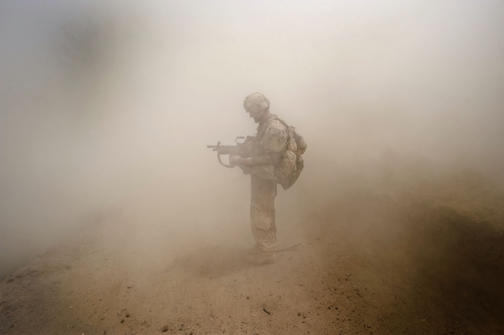 A soldier seen in the dust after a blast from an improvised explosive device while on a combat operation in Panjwa'i District, Kandahar, Afghanistan.  (Credit Image: © Louie Palu/ZUMA Press) FROM THE BOOK FRONT TOWARDS ENEMY. USE RESTRICTED TO BOOK REVIEWS ONLY