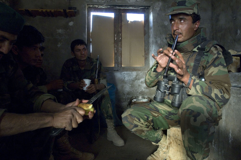 An Afghan soldier plays a flute while others peal potatoes on the front lines in the Howz-e Madad area a day before a combat operation against Taliban insurgents in Zhari District, Kandahar, Afghanistan. (Credit Image: © Louie Palu/ZUMA Press) FROM THE BOOK FRONT TOWARDS ENEMY. USE RESTRICTED TO BOOK REVIEWS ONLY