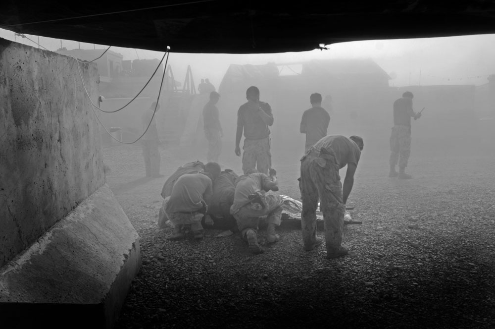 Canadian soldiers shelter a casualty outside a field hospital from a helicopters dust before moving him to a Medevac for transport to Kandahar Airfield in Zhari District, Kandahar Province, Afghanistan.  photo Louie Palu/ZUMA Press © FROM THE BOOK FRONT TOWARDS ENEMY. USE RESTRICTED TO BOOK REVIEWS ONLY