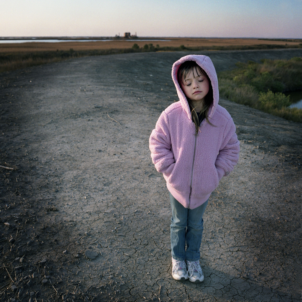 January 2009 Juliette Brunet stands on the small flood protection levee across the street from her house on Isle Jean Charles. A natural gas pumping station is visible on the horizon. Juliette lost both of her parents when she was younger and is being raised by her uncle who is bound to a wheelchair. Residents of the Island are committed to staying in spite of hardships brought by massive coastal erosion and coastal contamination after the BP oil spill.  Only 70 or so residents remain, down from 300 at it's peak. Photo:Kael Alford/Panos Pictures