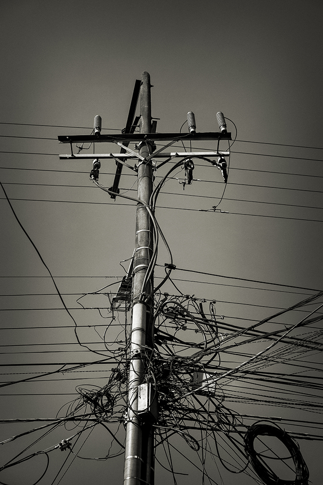 A mass of electrical cables converge on a single pole.