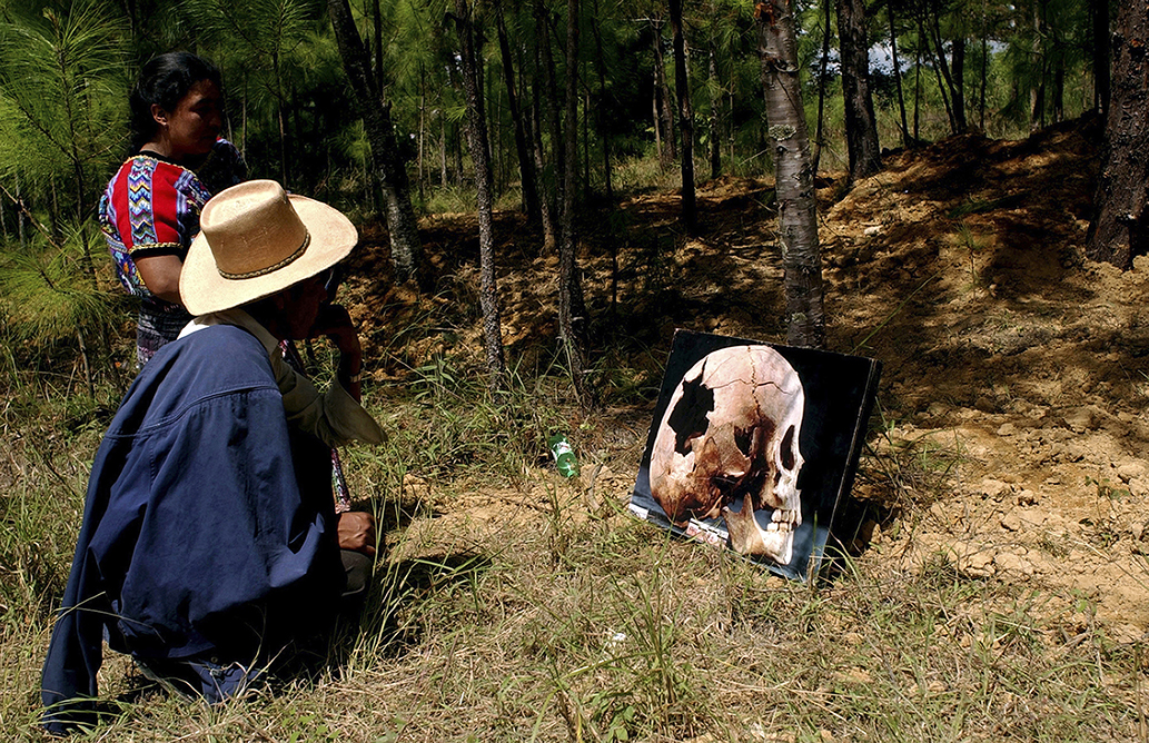 Lorenzo Cuxil and Felicita Oligaria look at a picture of a  victim killed by the Guatemalan Army  in a former military base in Comalapa, 80 km west from Guatemala City, Nov. 2, 2004. Guatemalans  honor their deceased loved ones on Nov. 1 and 2. (Ap Photo/Rodrigo Abd)