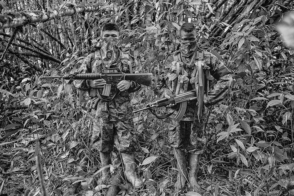 Angél 14, and Daniel (right), 16, members of the ELN Che Guevara Front pose for a picture at their camp in Choc. The Che Guevara front operates on the Pacific coast of Colombia patrolling important corridors to allow the export of cocaine to the Pacific Ocean and into Mexico. February 17, 2014.