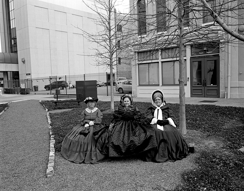 Montgomery, Alabama, 2011. To celebrate the 150th anniversary of the inauguration of President Jefferson Davis, Civil War re-enactors hold a rally in downtown Montgomery, the first capitol of the Confederacy. Perhaps by coincidence, these women, waiting for the rally to begin, are sitting on a park bench where Rosa Parks boarded the city bus she was arrested on in 1955, which helped launch the Civil Rights movement.