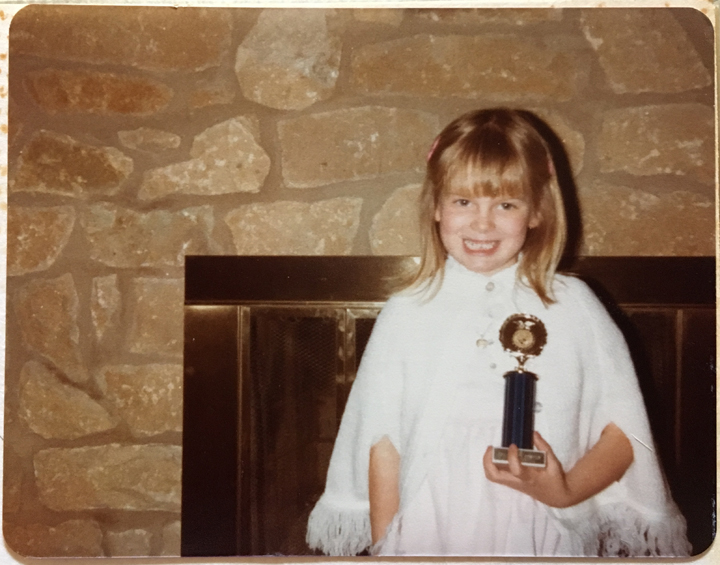 Q1_2_Amy, age 5, with her trophy from the kindergarten poster contest
