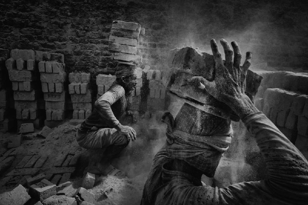 "Bangladesh, The technique of collecting bricks is well established. The men crouch down and using both hands, simultaneously place two bricks on a flat piece of wood resting on their head. But every movement stirs up a fine cloud of dust that covers them completely as it settles, transforming them into earth statues and endangering their health. 20 km east of Dacca, the periphery reveals many brick factories where men, women and very often children work in difficult and dangerous conditions. In this industrial complex, men prepare the earth using a mold to make bricks of gray color. After drying in the sun, they will go into a giant oven; a sort of long tunnel similar to those of coal mines. Overwhelmed with dust, in an infernal heat, women and children carry the bricks outside in wheelbarrows. With about 11,000 brickworks across the country, Bangladesh is struggling to meet the construction demands of a rapidly growing population. Armies of workers including women and children suffer the hard manual labor, in extremely poor conditions, for merely $1 per day. Working 12-18 hours, without access to fresh water or decent food, children as young as 4 contribute to the monumental task of producing 1500 bricks per person per day. Families live in makeshift camps near the factories breathing air filled with arsenic and particles of burnt plastic. Despite the 2011 directives from the OECD and the UN, holding multinationals accountable for workers rights and good labor practices all along the manufacturing chain, the reality on the ground is rather substandard. Several associations have launched campaigns under the name ""Blood Bricks"", to heighten awareness around what is essentially a form of slave labor. Particularly active in India, unions, ONGs and other human rights organizations are staging events to inform local populations and mobilize workers in order to improve working conditions, increase pay rates and above all, eliminate child labor which leaves kids uneducated, exploited and trapped in poverty."
