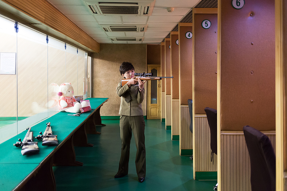 "Kim Hyang, 22 years old, works at the ""Meari Shooting Range"" (Pyongyang, DPRK, May 16, 2017). I asked her to pose for a photograph while she was preparing and checking the rifle in her hands. I did not tell her anything about the posture and facial expression."