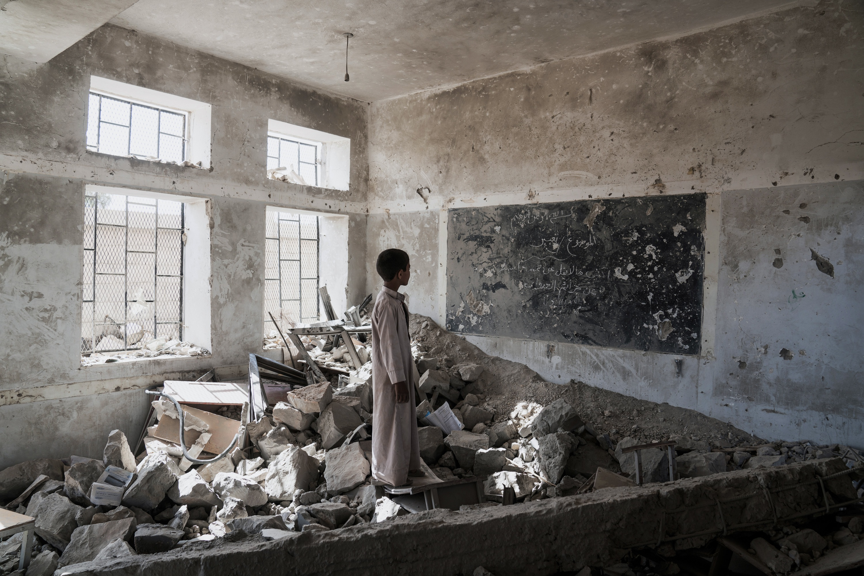 AAL OKAB SCHOOL , SAADA CITY, YEMEN - 24 APRIL 2017  A student at the Aal Okab school stands in the ruins of one of his former classrooms, which was destroyed during the conflict in June 2015. Students now attend lesson in UNICEF tents nearby.