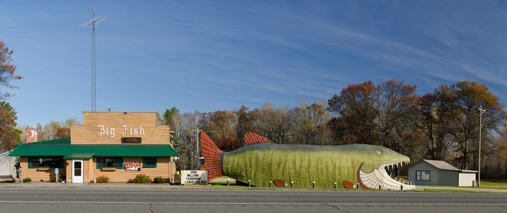 "Photograph of huge fish building, part of The Big Fish Supper Club, a landmark restaurant on US Highway 2 in Bena, Minnesota. The iconic ""Big Fish"" is a 65-foot long open-mouthed muskie. Fashioned from wood and painted tar paper, the 65-foot long, 15-foot wide fish, a muskie, was built in 1958 as a hamburger and ice cream stand by sculptor Wayne Kumpla. Al & Amy Hemme purchased The Big Fish Supper Club and Resort in May 2010. The Big Fish Supper Club and Resort 456 U.S. 2 Bena, MN 56626-1000 Phone: (218) 665-2299 Email: info@bigfishsupperclub.com"