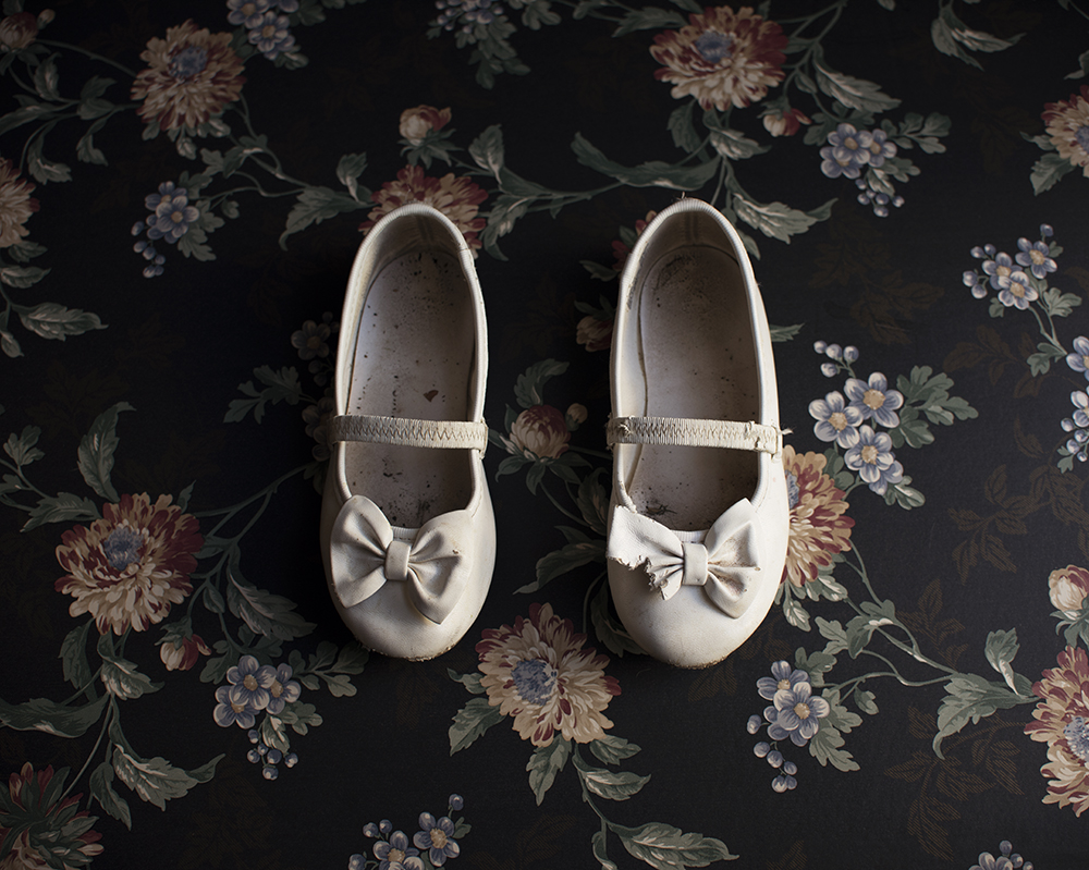 childs worn white shoes on floral background