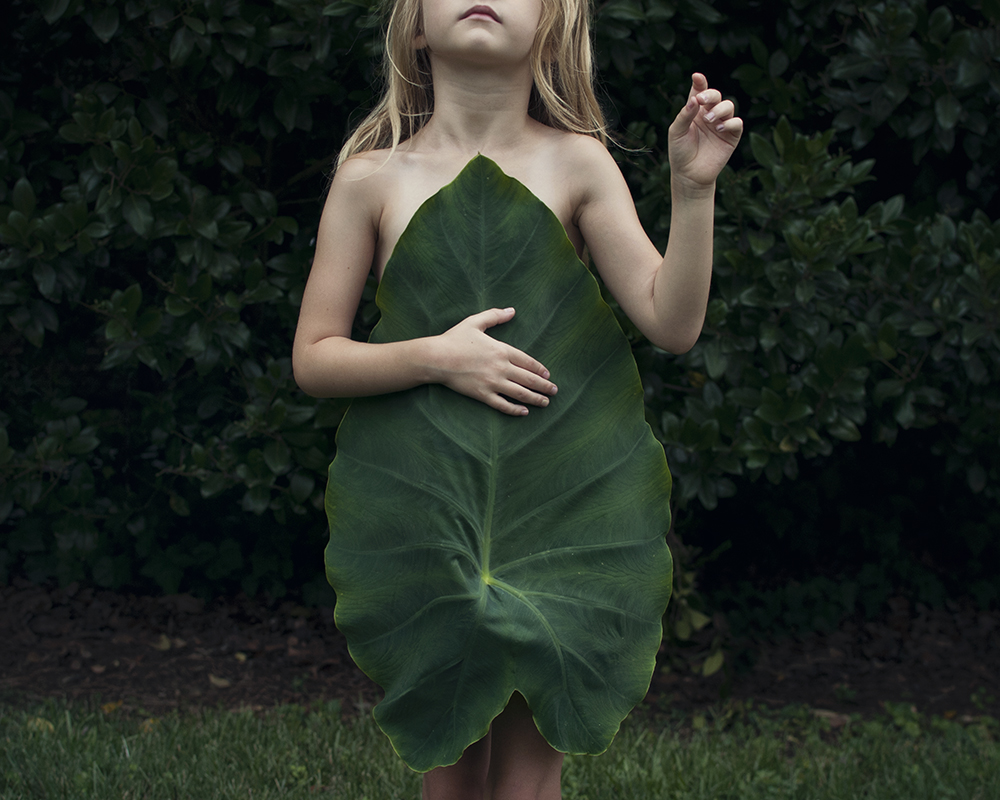 young girl with elephant ear leaf