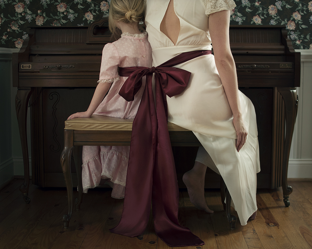 mother and daughter sitting on piano bench, tied together by one sash