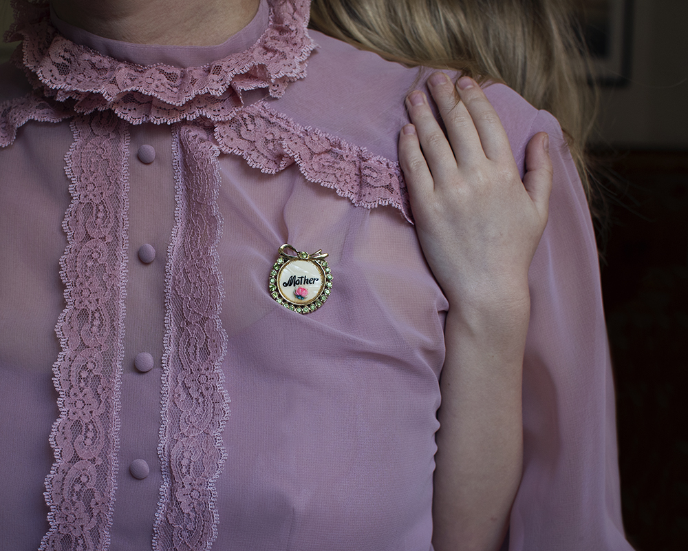 women wearing brooch that says mother.