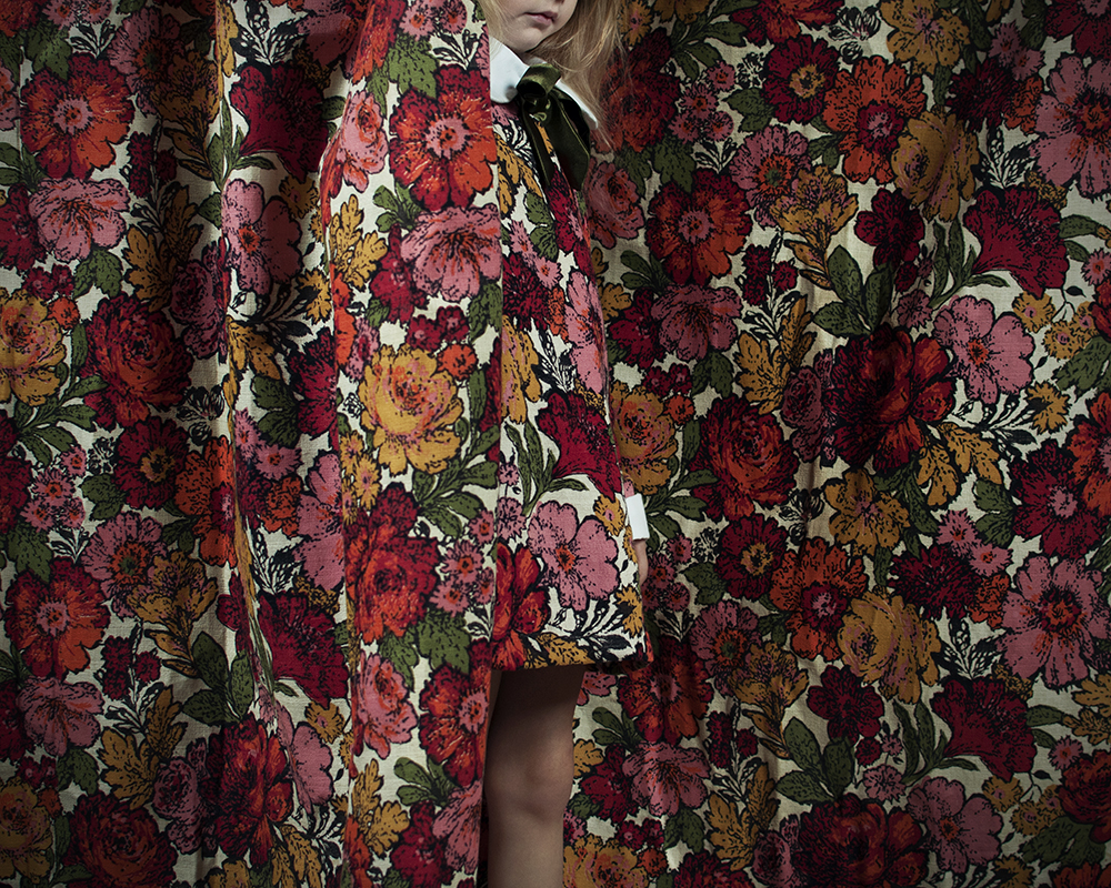 Young girl with floral dress on in matching curtains