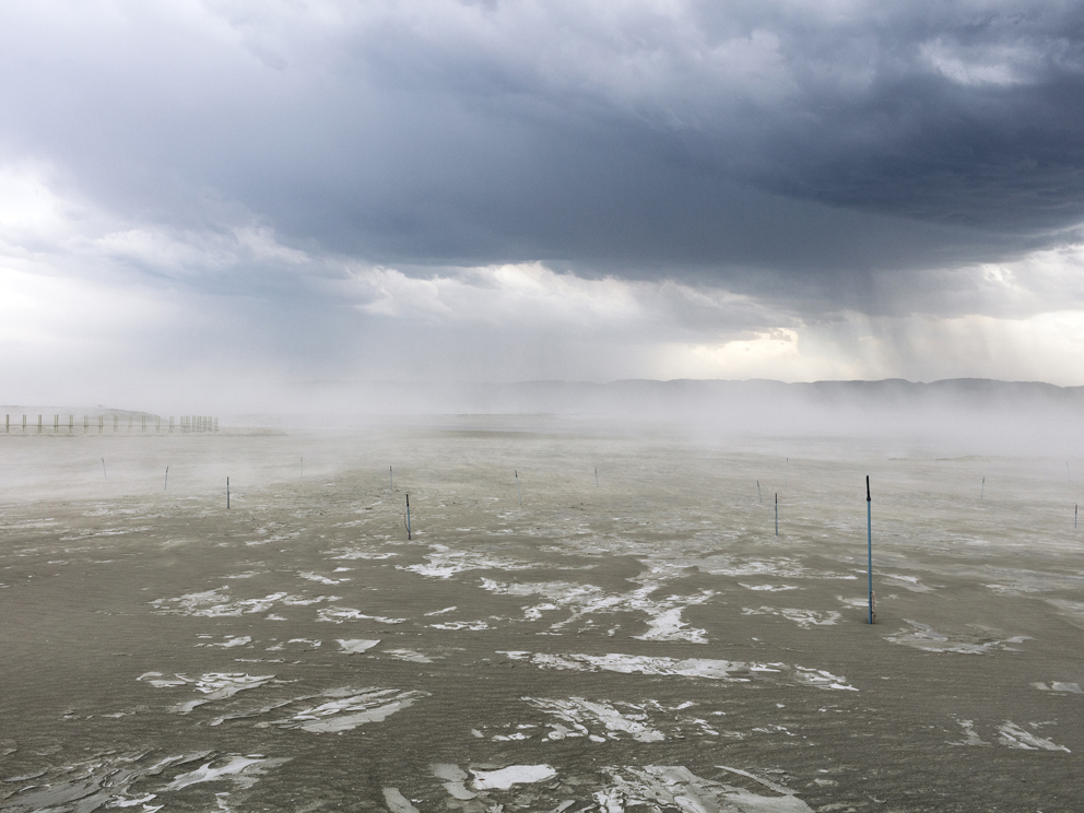 """02a - Fraser Alexander Tailings (Lonmin – Western Plats – Dam 5 Tailings Complex), Wonderkop, Marikana, North West, Western Limb Storm clouds hang overhead as strong winds carry dust tailings into the community. Informal settlements around mining operations in Marikana and the surrounds have been directly affected by dust pollution, further exacerbated in windy conditions. Dust suppression systems have been installed on the tailings in an attempt to control high dust levels. However, with communities living in close proximity to these tailings, the efficacy of such systems is limited. Community members complain that the high dust levels contaminate food and water, and many children in the area suffer from asthma and other respiratory-related illnesses. Professor Eugene Cairncross from the Cape Peninsula University of Technology writes, """"Health impacts from dust include breathing and respiratory systems, damage to lung tissue, cancer and premature death."""""""