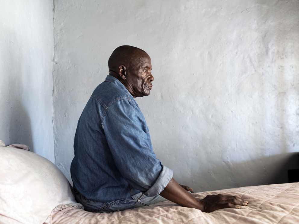 """76 – Otto Lekalakala, 67, Bapong, Newtown section, North West, Western Limb Bapong, a sprawling village with a population of approximately 40 000, is the epicentre of the Bapo Ba Mogale royal community. The Bapo people first settled here around 200 years ago on land that holds some of the richest platinum deposits in the world. Lonmin was established here in 1970 on the basis of a lease agreement to pay the community royalties on the minerals extracted. Otto arrived in Bapong in 1989, working at the now-closed Newman Shaft for eleven years as an underground rigger, before moving to the """"change house"""", where he saw out the remainder of his working years.   Now a pensioner, Otto is an active representative and concerned resident of Bapong's Newtown section. In 2015, he was summoned to the royal palace, shortly after presenting a letter he had signed on behalf of the community pertaining to various grievances. These grievances included Newtown councillors not performing their duties, lack of employment opportunities, and members of the tribal authority not participating in meetings with the chiefs to hear the community's concerns. Adding to the general air of dissatisfaction among the community, a controversial R664m equity deal had recently been signed between Lonmin and the royal council, which would see mineral royalties converted into company shares. Otto was among those who voiced dissatisfaction with the agreement, believing the community would not benefit. This, he believes, also strained his relations with the royal palace. On his arrival, Otto stood before a chamber of more than 100 people who quizzed him on the grievances contained in his letter. Upon insisting they speak directly to the community about them, Otto claims senior members of the Bapo Ba Mogale Tribal Authority proceeded to beat him. A friend later took him to a local clinic, where he was treated for a fractured left hand and contusions to his body. Otto says he went with witnesses to"""