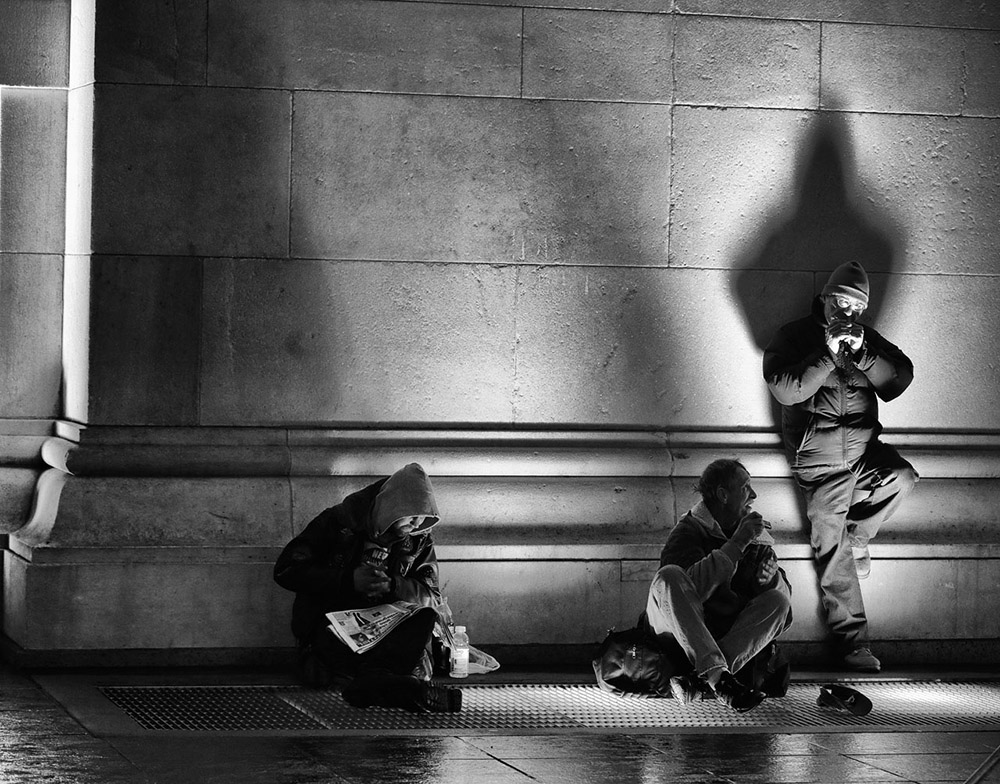 Reading Series--Washington square Park, December 22, 2014. Man reading newspaper as others play harmonicas under the Arch. exclusive photo by Lawrence Schwartzwald