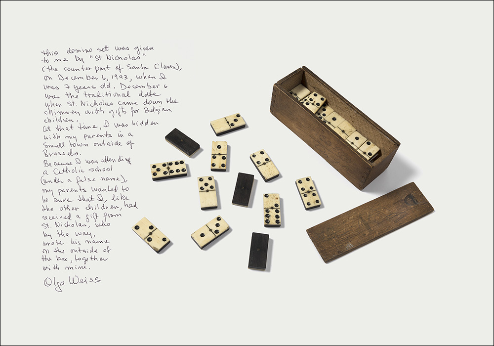 "Olga Weiss Antwerp, Belgium, May 26, 1936 - Domino Set Brussels, Belgium, 1943 Reflections by Olga Weiss This domino set was given to me by ""St. Nicholas"" (the counterpart of Santa Claus), on December 6, 1943, when I was 7 years old. December 6 was the traditional date when St. Nicholas came down the chimney with gifts for Belgian children. At that time, I was hidden with my parents in a small town outside of Brussels. Because I was attending a Catholic school (under a false name), my parents wanted to be sure that I, like the other children, had received a gift from St. Nicholas, who by the way, wrote his name on the outside of the box, together with mine. Olga Weiss"
