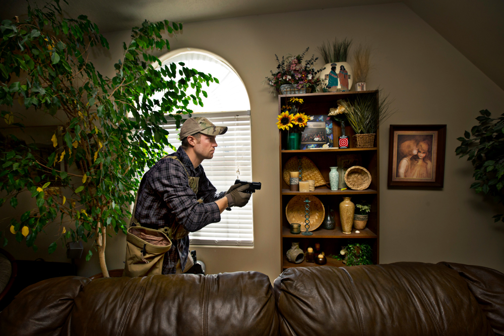 "Ace Spade practices drawing his hand gun in the living room of a members home during a training exercise.  ""Like a lot of people I want to have a plan. A want to have a group of people I can rely on not only for protection but also to protect. If something were to happen, civil unrest or a natural disaster and our government was not able to protect us, I don't want to be one of those helpless people that's just gonna fall by the wayside to irrelevance or insignificance.  I want to actually do something in my community to show that I'm willing to do what it takes.  I'm a patriot. I'm willing to bleed on that flag so those strips stay red,"" says James Wood."