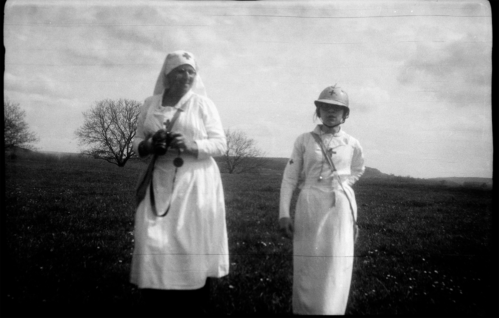 "Two nurses, a grandmother and her grandchild, walk around the battlefield looking for reenactors pretending to be wounded in Noyon, France, April 2018. Photo taken with the Kodak Vest Pocket, also known as ""The Soldier's Kodak"", a camera largely used by combatants during WWI. The Vest Pocket produced a great deal of the amateur archival images of the conflict we have today. The image is part of the series ""Nostalgie de la boue"" (Nostalgia for Mud), a work in progress about memory a century after the end of the Great War."
