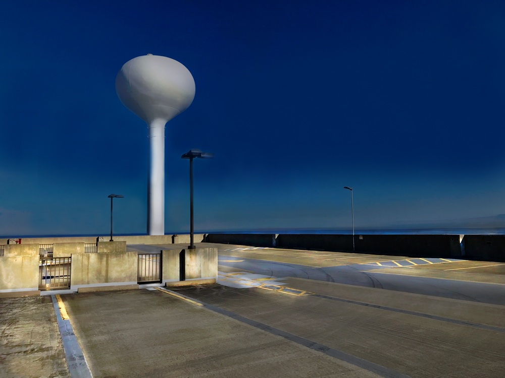 Color photo of the top floor of a parking garage and water tower in Lakeshore, Mississippi.