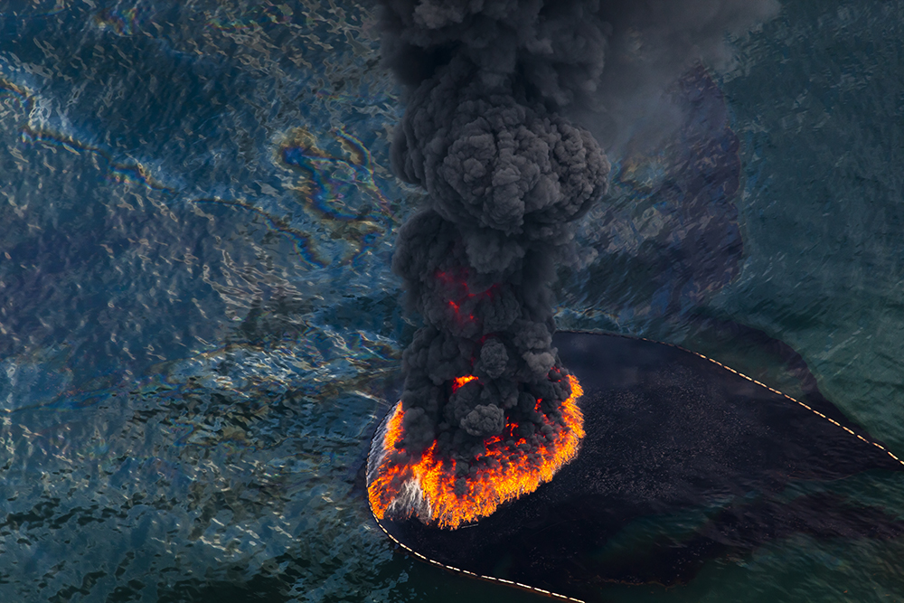 A plume of smoke rises from a burn of collected oil, May, 2010. A total of 411 controlled burns were used to try rid the Gulf of the most visible surface oil leaked from the BP Deepwater Horizon. ©Daniel Beltra, courtesy Catherine Edelman Gallery, Chicago
