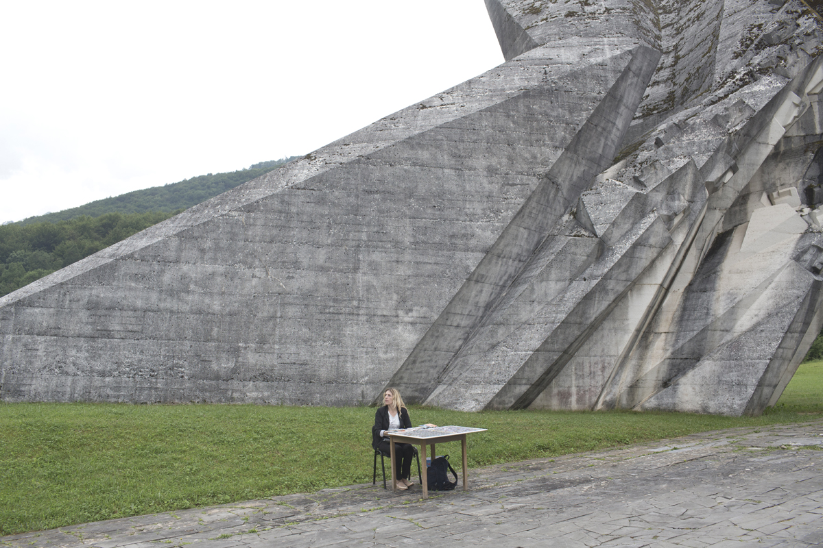 A souvenir seller waits for customers as she sits next to a monument to the WWII Battle of the Sutjeska, Tjentiste, Bosnia and Herzegovina, June 17, 2017. Thousands of monuments of all shapes and sizes were erected in Yugoslavia throughout the 1960's and 1970's to commemorate important historical events. A large number of the monuments were heavily damaged or destroyed on purpose in the 1990's conflicts. Those that survived are still visited by Yugoslavs and people who feel nostalgia for the old country.