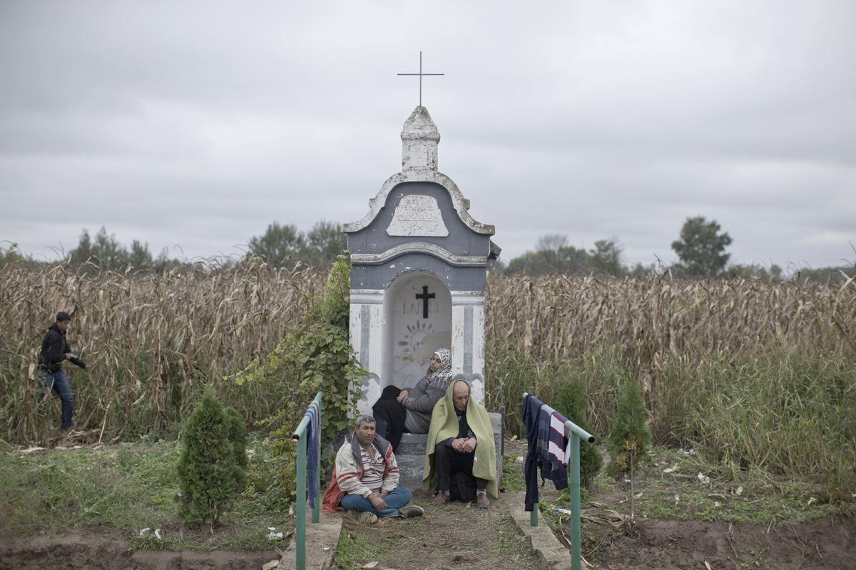 Refugees from Syria rest at a roadside chapel on the border line between Serbia and Croatia, Sept. 26, 2015. The fields around the southern portion of the Serbo-Croatian border where this small chapel is located are littered with uncleared minefields, left over from the Yugoslav wars in the 1990's. In 2015, at the height of the European refugee crisis, hundreds of thousands of refugees fleeing from war in their home countries, passed through farms, fields and towns that were once on the front lines of the Yugoslav conflicts.