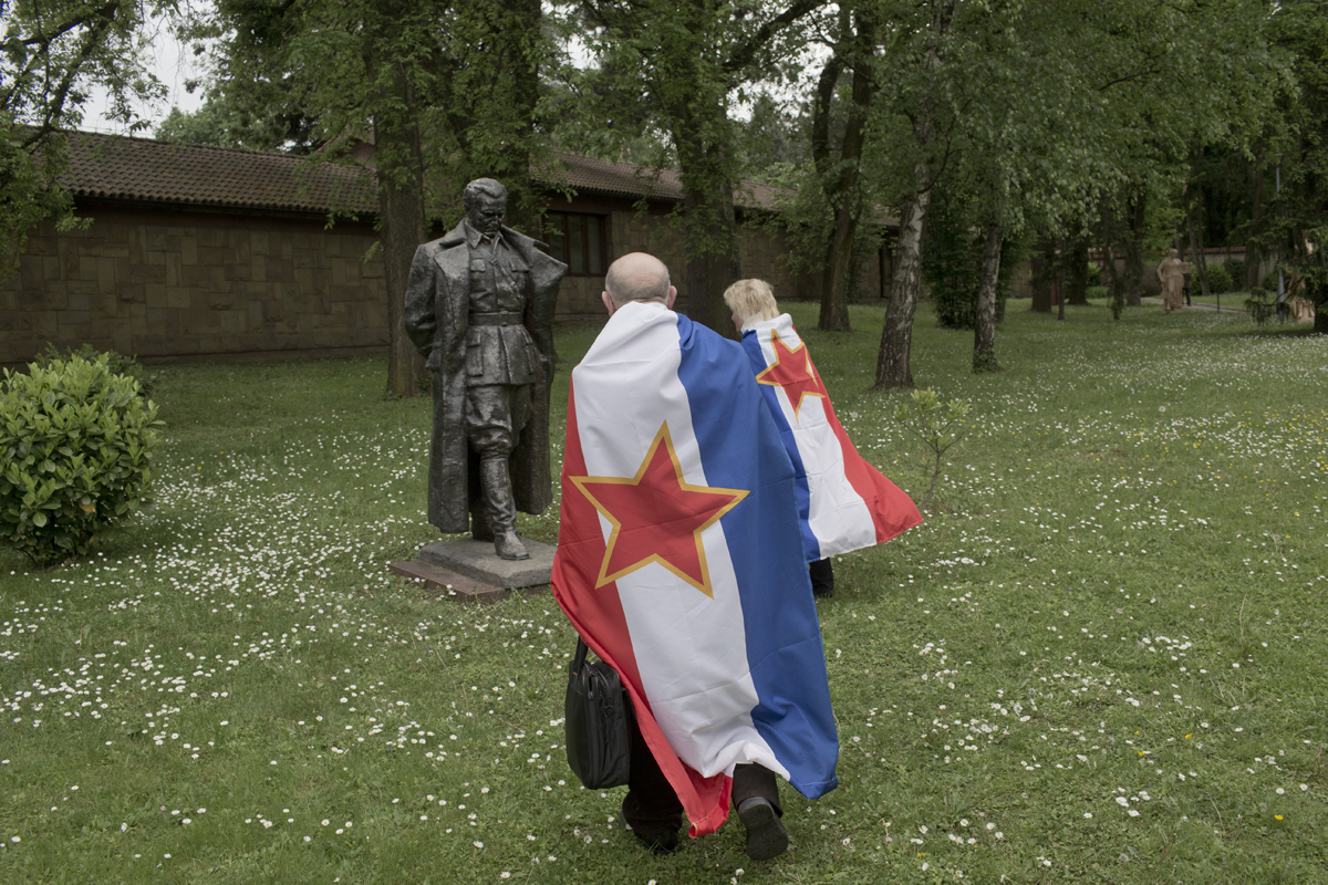 Two people covered in Yugoslav flags approach a statue of former Yugoslav leader, Josip Broz Tito, inside the House of Flowers memorial complex that houses his gravesite, Belgrade, Serbia, May 4, 2017. The House of Flowers, Tito's final resting place, attracts hundreds of Yugoslavs and Yugonostalgics each year on May 25, the day Tito was born, and on May 4, the day he died. Visitors are rare throughout the rest of the year.