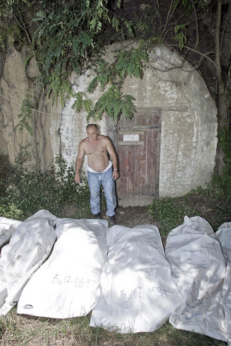 A municipal worker smokes a cigarette next to bags containing remains of Kosovo Albanian victims, discovered inside a Serbian special police training facility after the fall of the Slobodan Milosevic regime, Belgrade, Serbia, August 9, 2005. The remains of Kosovo Albanian victims of atrocities in the 1998-1999 war were moved from Kosovo to Serbia proper before the conflict ended in order to disguise or diminish the scale of the crimes committed by some of the Serb forces.