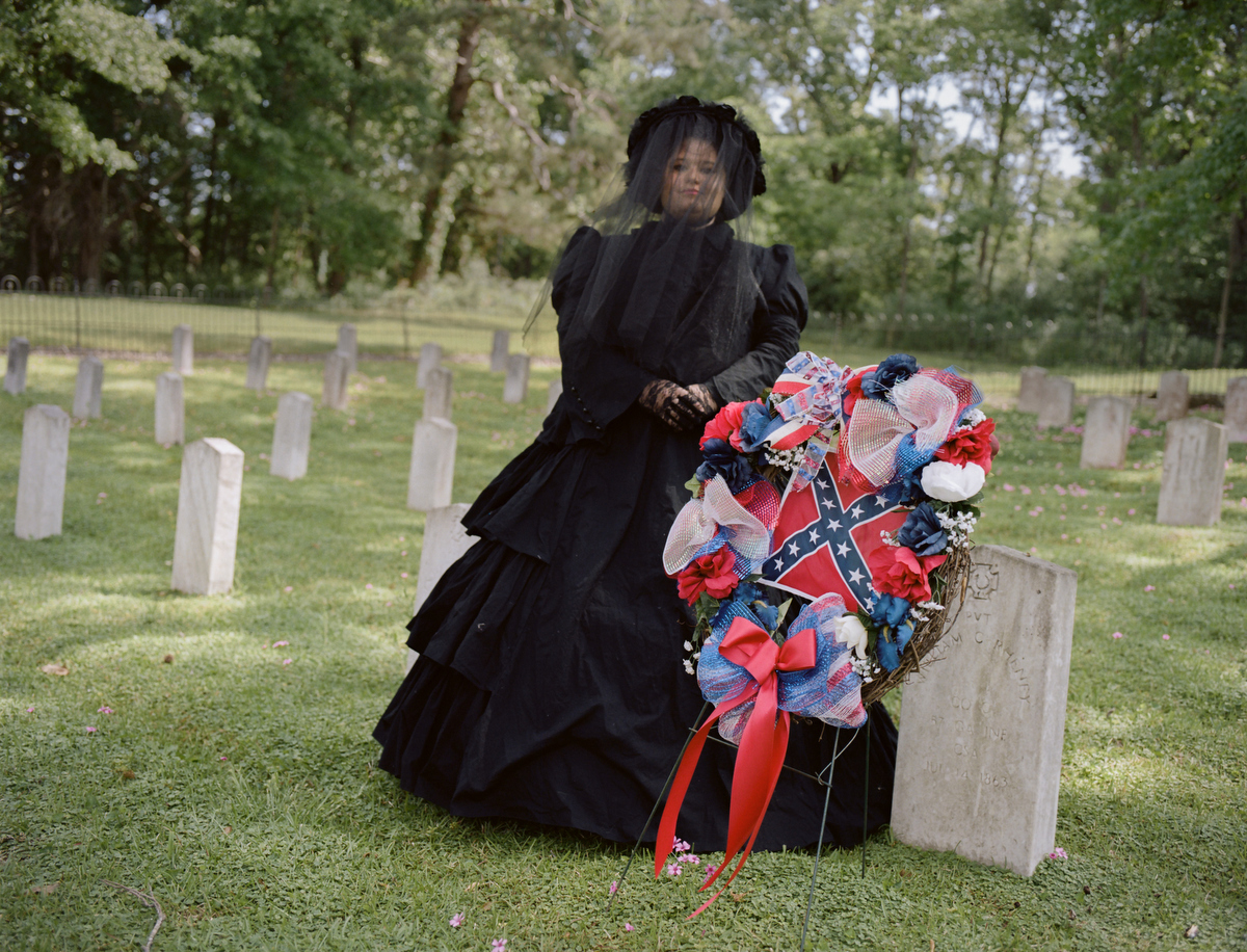 Tara Bradley poses for a portrait in her official Òmourning gearÓ. She is a member of a group called the Order of the Confederate Rose. Though similar to groups like Daughters of the Confederacy, members of this group insist that they are not political and are open to all people. . On April 21, the group laid wreathes at a Confederate cemetery in Raymond, Mississippi for Confederate Memorial Month. The keynote speaker from the local Sons of Confederate Veterans group mentioned Hitler, the KKK and David Duke in his speech. One member of the Roses left in the middle, but it was later discovered that she did not leave in protest but because her feet hurt. After the ceremony, when pushed on dressing up as confederate slaveholders, members repeated false statistics like only 5 percent of Southerners owned slaves (in Mississippi, it was 55 percent), and argued that people also dress up as Union soldiers. When it was pointed out that no one dresses up like slaves, one woman exclaimed, ÒÒWeÕd love to have someone that would!Ó All of the women present boasted about volunteer work and civic duty and none thought their costumes or activities were racists or offensive. Groups like the OCR help keep the traditions of the Confederacy Ð and itÕs racists policies Ð alive and well.
