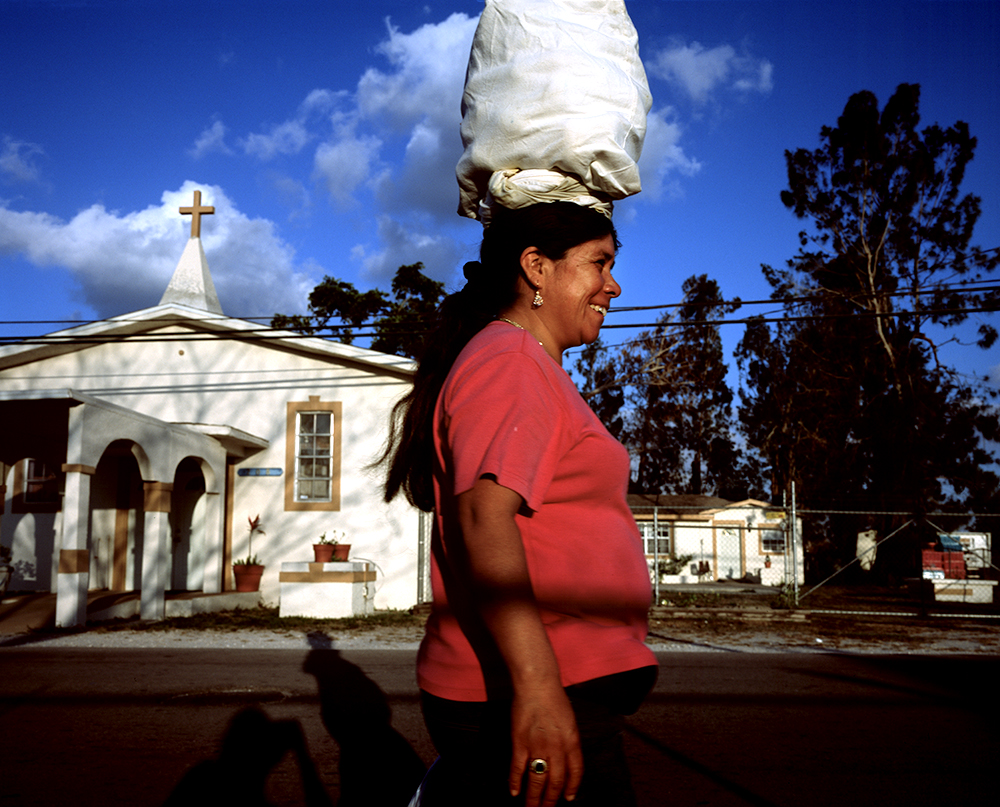 Untitled, Migrants in Immokalee, Florida 2006 A Latin American immigrant carries home her things on top of her head in the agricultural Florida town of Immokalee.  This town was the lcoation of the seminal William R. Murrow documentary, Harvest of Shame, about agricultural practices there. Today the poor black laborers have been replaced with those who originate from primarily Caribbean and Latin American countries.