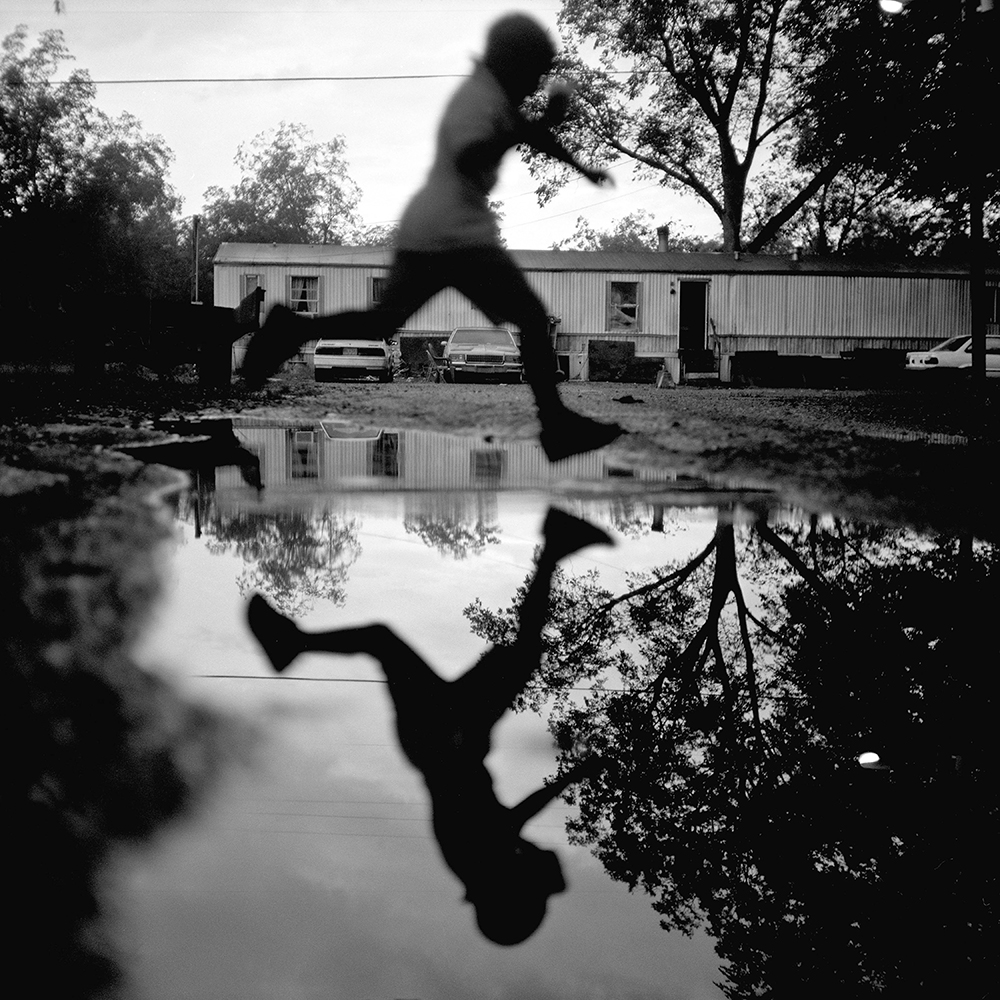 DUNCAN, MS - SEPTEMBER 16: A young boy jumps over a water puddle after a rain storm in Duncan, MS, on Thursday, September 16, 2009.