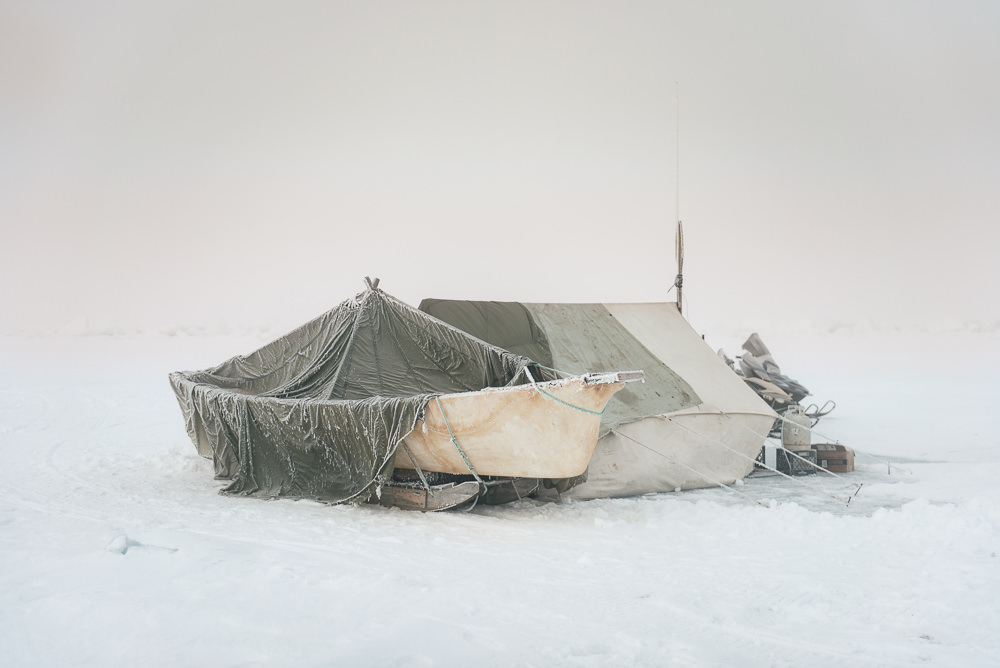 "This camp, erected miles out on the sea ice, is the Iñupiaq home away from home. Despite spending months living in cramped and frozen quarters, the captain of Yugu crew prefers it. ""It is quiet here.""  This setup is typical of spring whalers, who spend months on the sea ice waiting for whales by their skinboat."