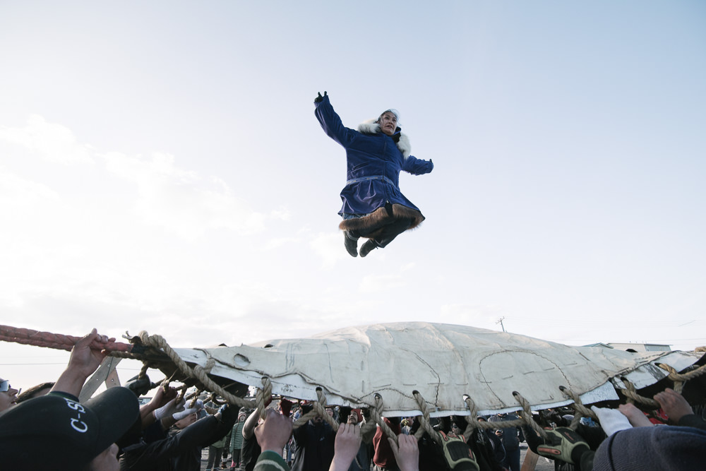 At Nalukataq in Barrow, Alaska, the Iñupiaq whaling festival, the village comes out to celebrate a successful whaling season and to give thanks to the whale for its gift. Here, successful whalers must do the blanket toss. They are thrown up to thirty feet in the air, and depend on everyone's hands to land safely. This trust goes back millennia, and ensures intimacy among the growing population in Iñupiaq villages.