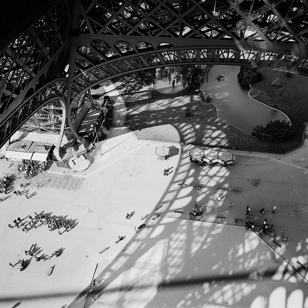 Pedestrians gathered in plaza beneath the Eiffel Tower in Paris, France.