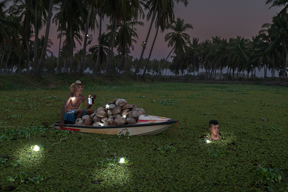 Cristobal Cespedes Lorenzo (51) sits on his raft while carrying coconuts across the river to his home in Copala, Mexico.  Cristobal and Francisco Manzanares Cagua (16) both work picking coconuts which they then sell to a company which makes cocounut butter and oil.
