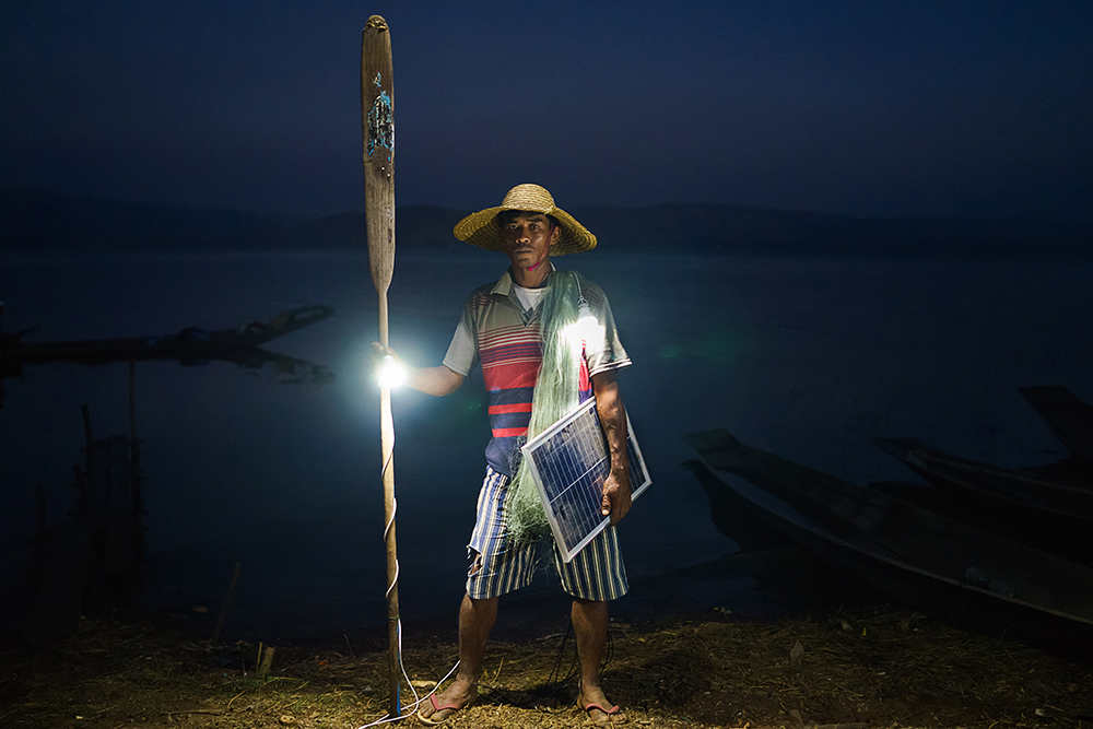 Ko Win Zaw Oo, 38, fisherman and father of 2 by his boat in Lui Pan Sone Village. Kayah State. Just 26% of Myanmar has access to electricity, at least half of whom live in cities. In rural areas, of the estimated 68,000 villages in the country, just 3,000 or so have any sort of access to power. Solar power is a viable source of energy which can rapidly improve lives overnight. The scenes have all been lit only by solar powered light bulbs which are contributing to the improvement in these people´s standard of living.
