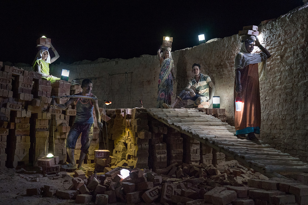 (June 5, 2015) Workers use solar lamps to collect newly baked bricks at night to be arranged in Amit Brickfield, Saipur, India. Roughly 1.1 billion people in the world live without access to electricity, and close to a quarter of them are in India, solar power is a viable source of energy which can rapidly improve lives. The portrait was set up using solar lights as the only source of ilumination.