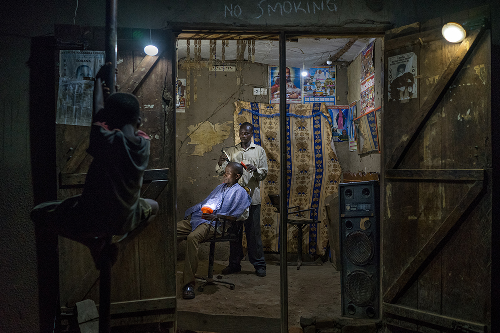 (May 31st, 2015) Denis Okiror (30) began using solar lights at his barbershop in Kayunga two years ago, he says most of his customers prefer to visit him in the evening. Electricity is a rare luxury in Uganda. The portrait was set up using solar lights as the only source of ilumination.